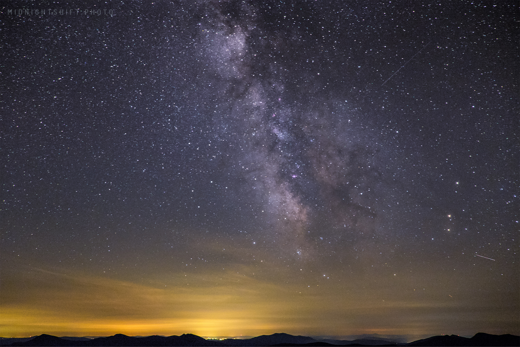 The Milky Way Galaxy can be seen above the lights of Lincoln New Hampshire from the fire tower.